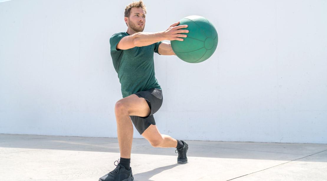 Man-Wearing-Green-Shirt-Doing-Rotational-Lunge-With-Medicine-Ball