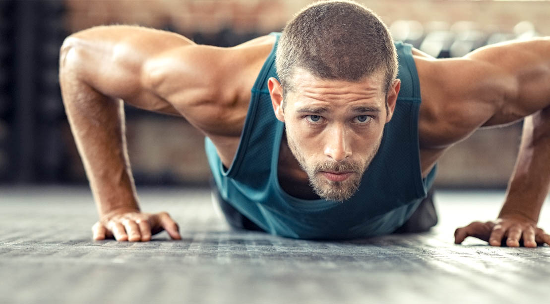 Fit man with a beard doing a bodyweight workout and doing a half rep pushup exercise