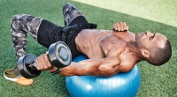 Man doing swiss ball bicep curl while working out outdoors