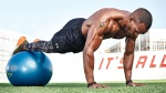 Man training outdoors doing plank with feet on ball