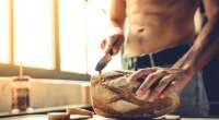 Muscular man cutting a loaf of fresh baked bread in his kitchen with a bread knife