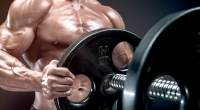 Muscular-Man-Putting-Additional-Plates-On-Barbell.