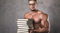 Muscular-Man-Wearing-Glasses-Holding-Stack-of-Books