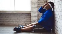 Overweight-Man-Frustrated-Sitting-Against-Wall-On-Floor