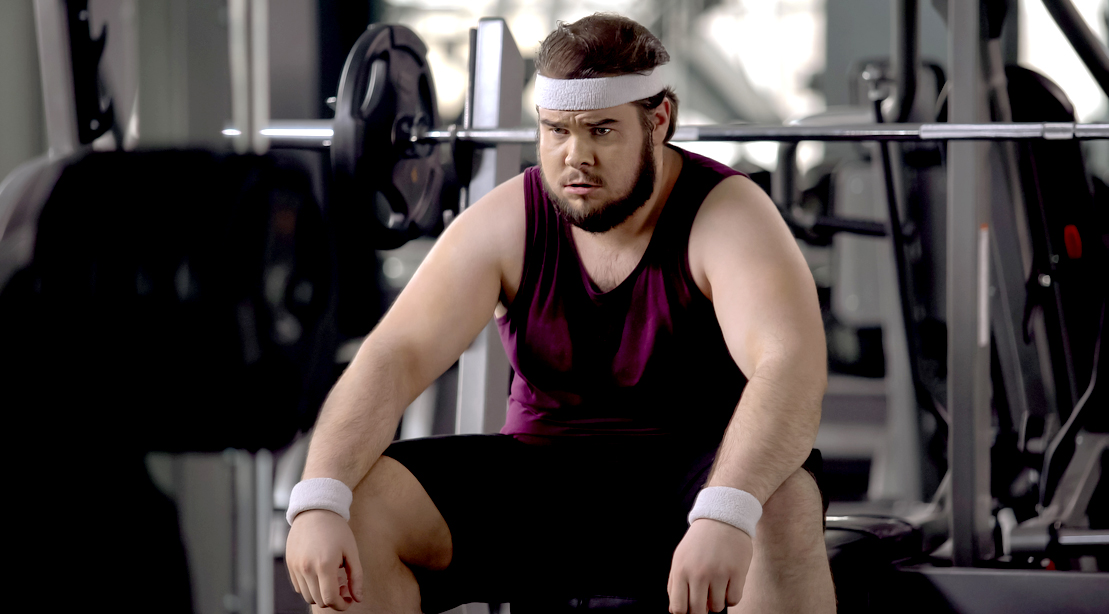 Overweight man sitting at a bench press and struggling to lose body fat
