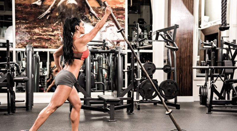 Female fitness model doing an upper body workout routine with a land mine press exercise