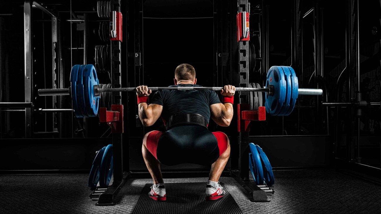 Power lifter at a squat rack doing a barbell back squat