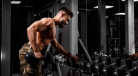 Man Lifting Dumbbells in the Gym