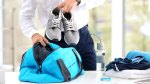 Business man packing gym bag with sneakers