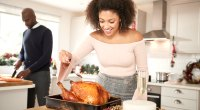 Couple-Preparing-Turkey-Dinner-Female-Basting-Turkey