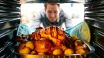 Man-Pulling-Roasted-Tukey-Covered-in-Bacon-In-Oven