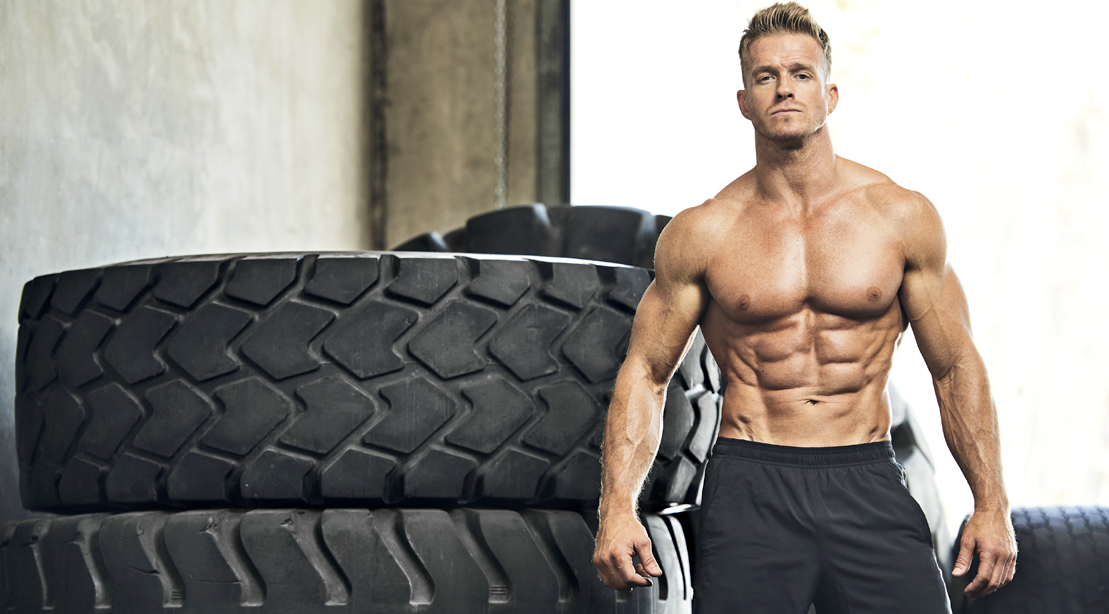 Muscular-Topless-Man-Standing-In-Front-Of-Tires