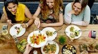 Three-Girls-Sitting-At-Restaurant-Eating-Healthy