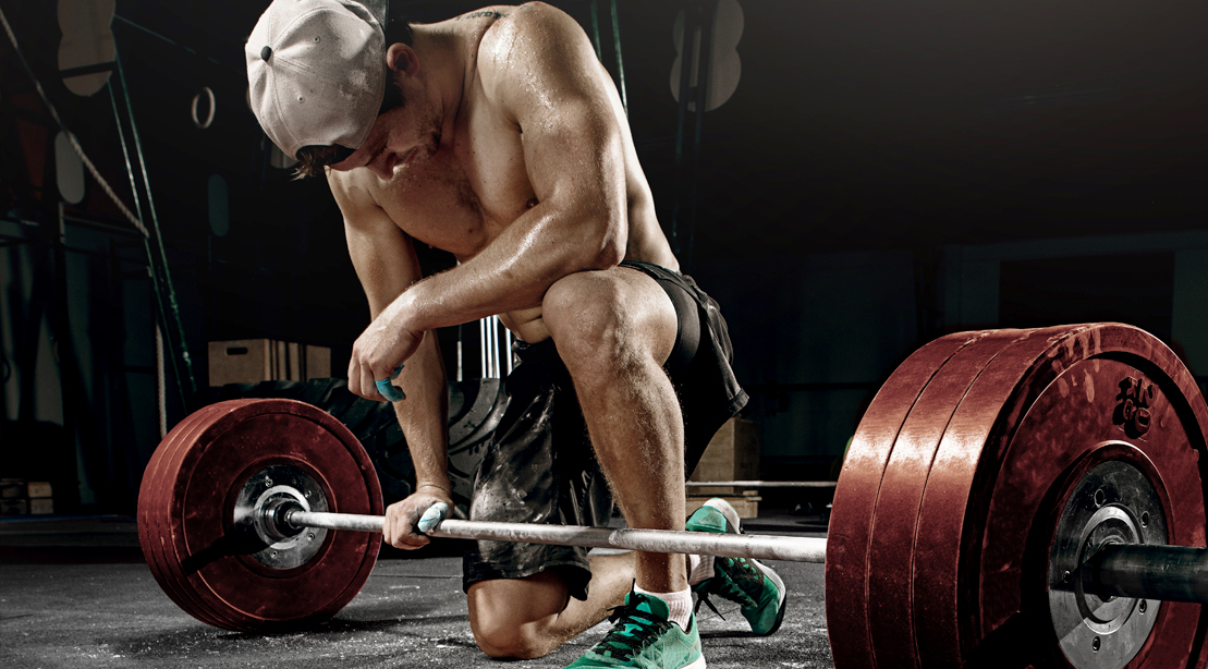 Tired muscular man experiencing a workout plateau due to performing hypertrophy finishers kneeling next to a barbell