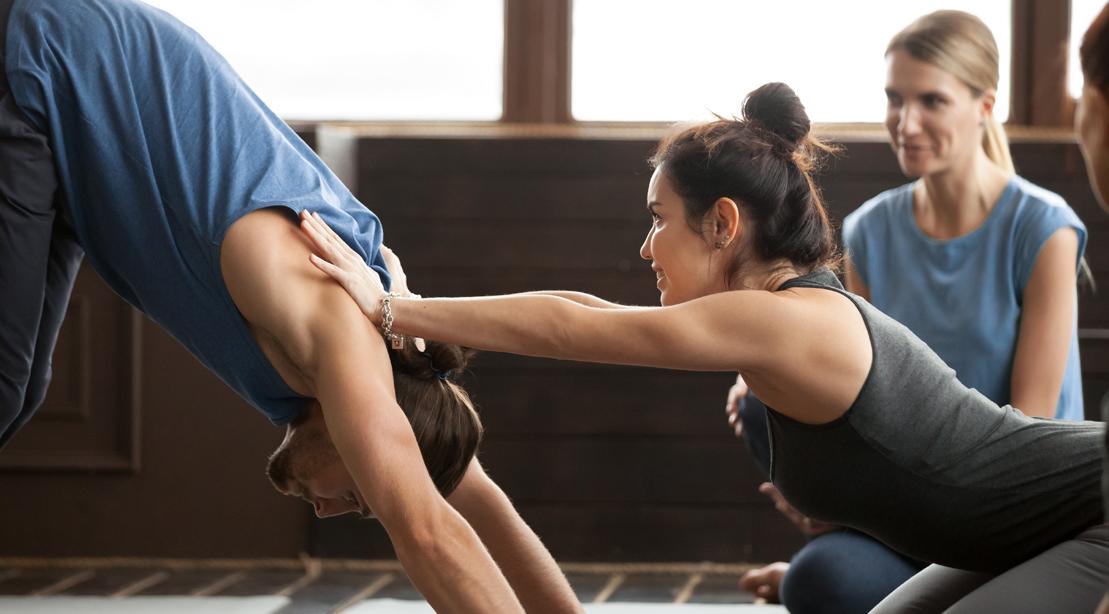 Yoga-Instructor-Healping-Guy-Do-Pike-Pose