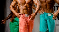 Physique bodybuilder competitors in trunks posing in a bodybuilding competition