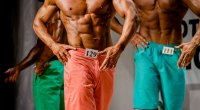 Classic physique bodybuilder competitors in trunks posing in a bodybuilding competition