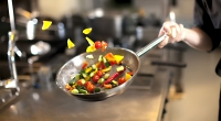 Chef-Tossing-Vegetables-In-Stainless-Steel-Pan