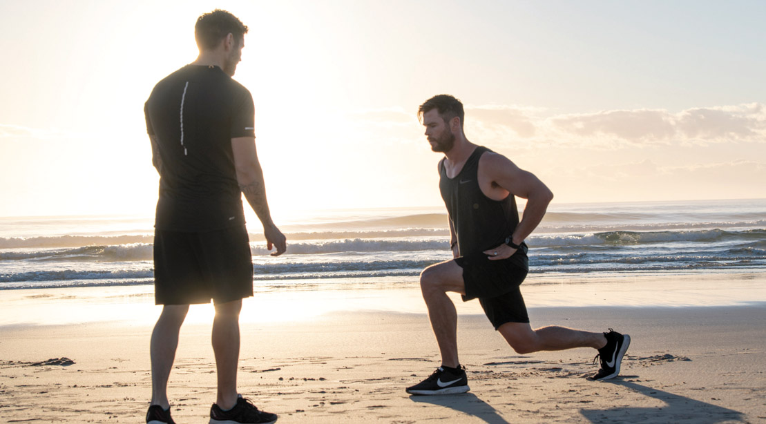 Chris-Hemsworth-Training-With-Luke-Zocchi-Lunges-On-Beach-Sunrise