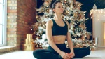 Female-Medititating-In-Front-Of-Christmas-Tree