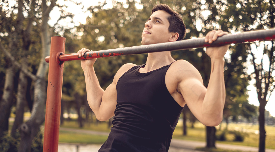 Fit man performing a pullup in the park
