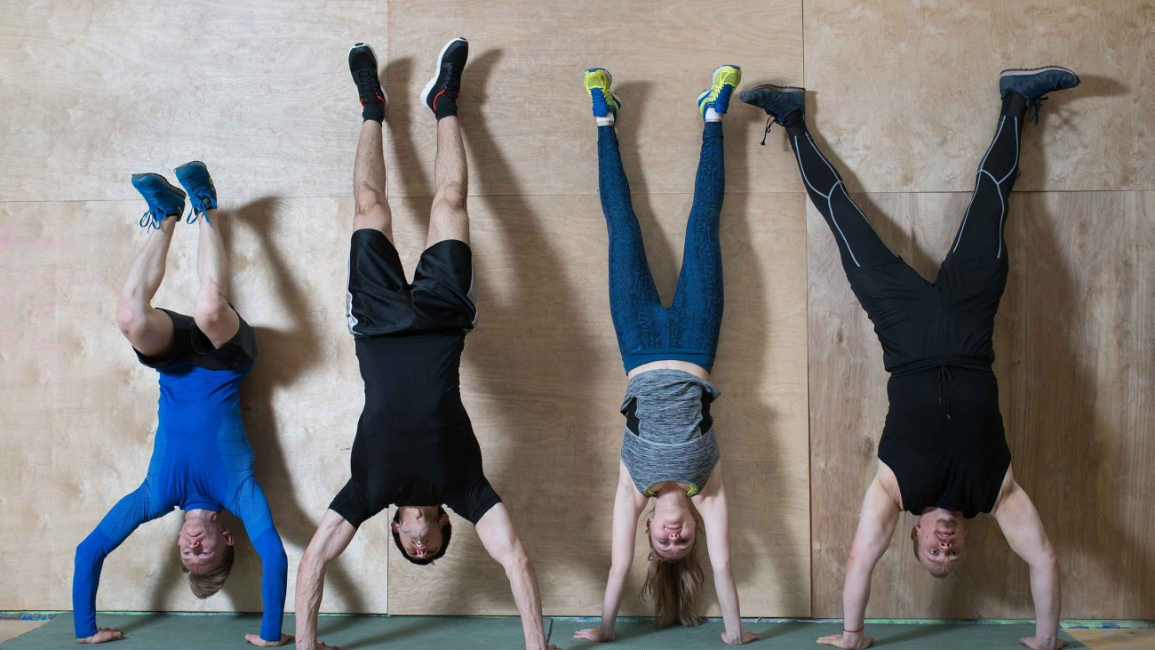 Group fitness class doing handstand pushup