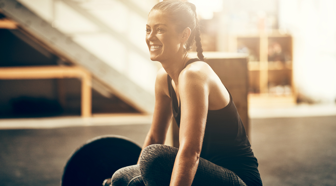 Happy-Girl-In-Gym-Sitting-On-Barbell for Exercise is Medicine