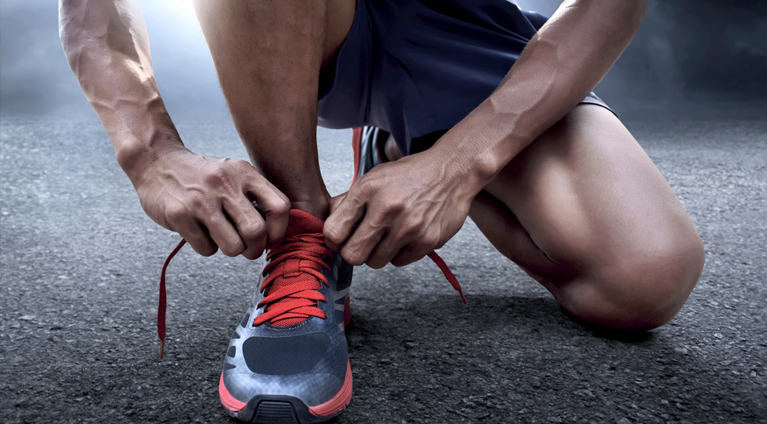 Male runner tying his running shoes in preparation for running a marathon