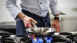 Man-Cooking-With-Stainless-Steel-Pan-On-Stove