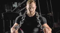 Muscular-Male-Holding-Chain-Around-Neck-and-Shoulder-Gym.