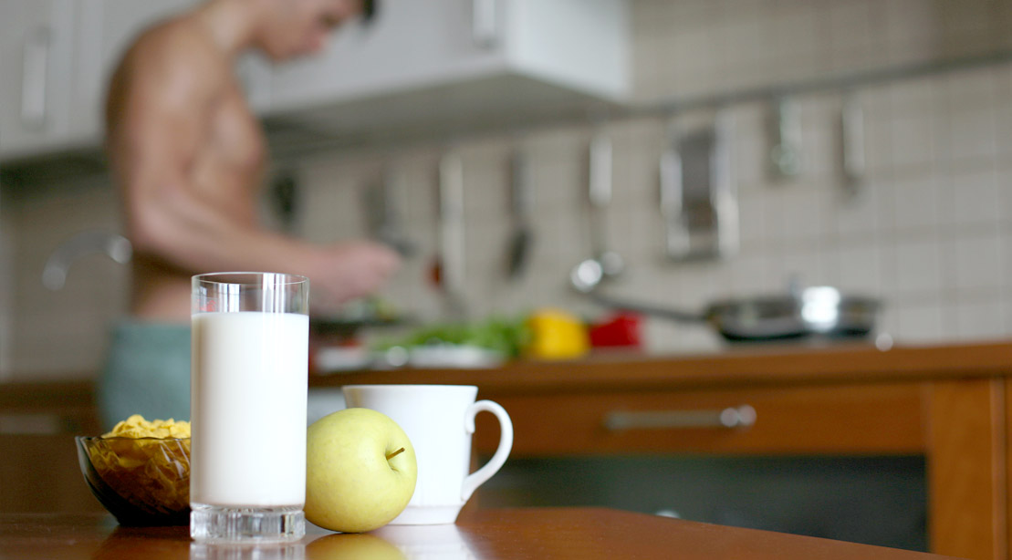 Muscular lean man cooking breakfast in the kitchen wearing a towel around his waist