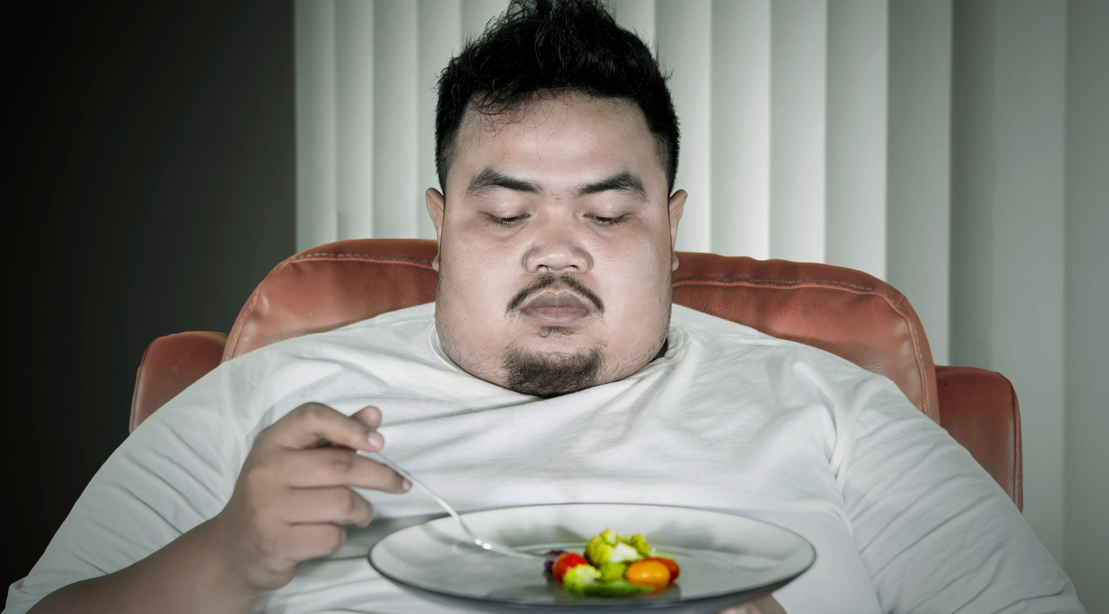 Obese-Person-Depressed-Eating-Tiny-Portion-Of-Vegetables