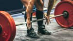 Powerlifter with chaulky hands grabbing a barbell against his shin ready to deadlift.