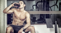 Topless-Male-Sitting-On-Bench-Post-Workout-Drinking-From-Shaker