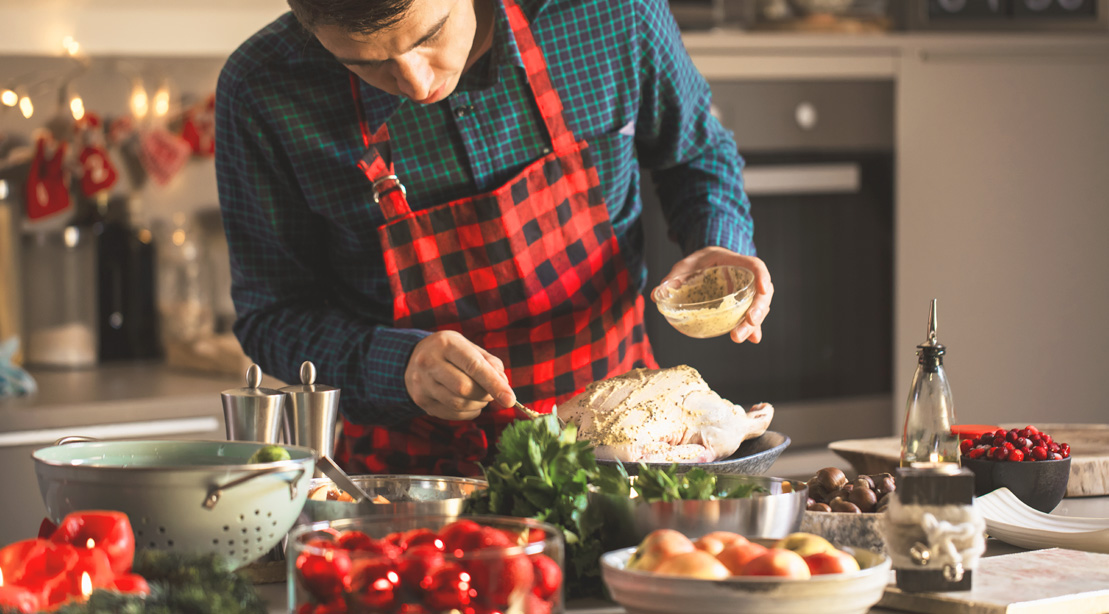 Young-Man-Preparing-Fowl-Spreading-butter-Christmas-Holiday-Meal