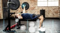 Fitness beginner working out his chest with a barbell bench press chest exercise with tech graphics imposed