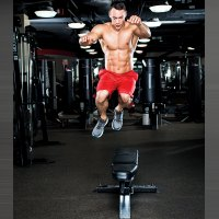 muscular man performing side jump and jumping over a bench
