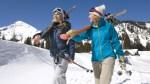 Female-Skiiers-On-Mountainside-Walking-In-Snow