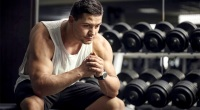 Male-Bodybuilder-In-Front-of-Dumbbell-Rack-Thinking-Pensive.