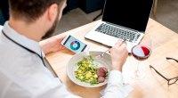 Man eating a salad at while at work and counting his calories and tracking his macros