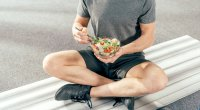 Man-Sitting-On-Bench-Eating-Salad