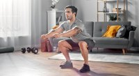 Man doing air squats at home in his living room