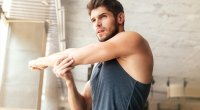 Man-Stretching-Arm-In-Sunny-Room