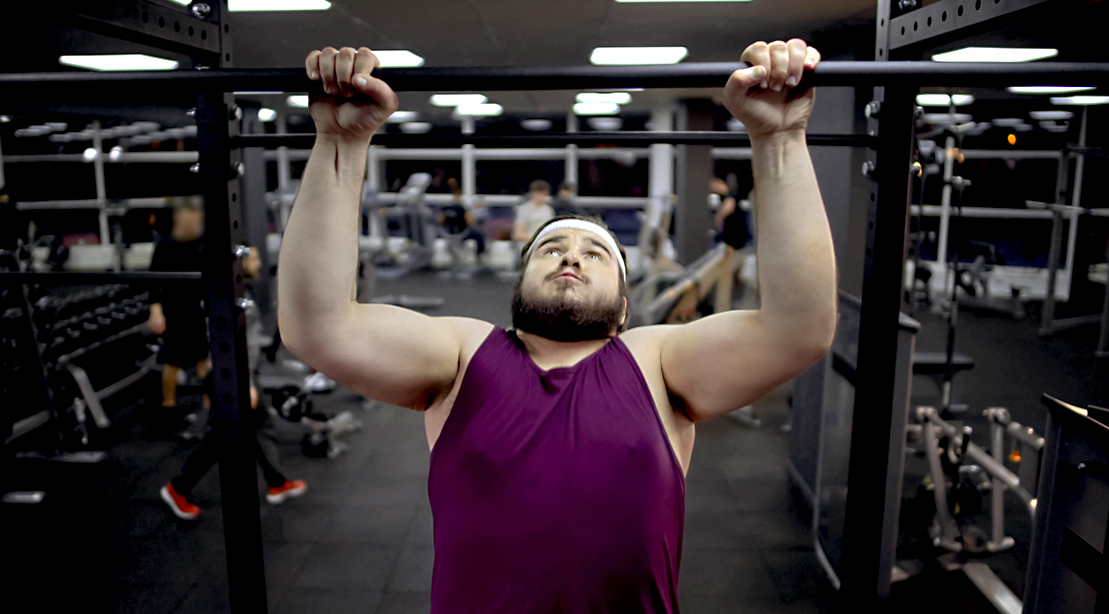 Overweight fitness beginner doing pullups