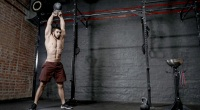 Topless-Muscular-Male-Performing-Overhead-Kettlebell-Swing