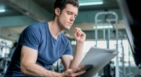 Young-Muscular-Man-Reading-Paper-Notes-In-Gym.