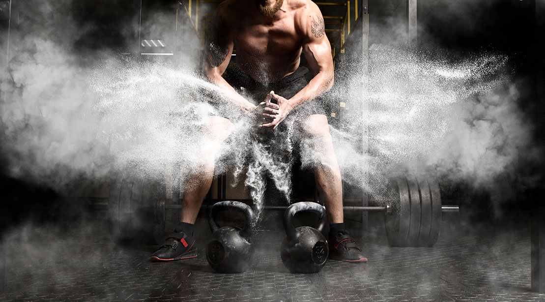 Fit male preparing for a kettlebell workouts and creating a cloud of chalk for extra grip