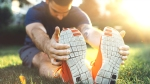 Athletic-Man-Wearing-Sneakers-Stretching-Body-On-Grassy-Field