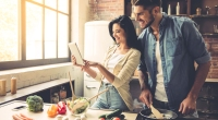 Couple-Learning-To-Cook-In-Kitchen-Lookiing-At-Ipad