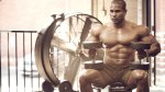 Bodybuilder Damien Patrick shirtless holding heavy dumbbells while sitting on a bench